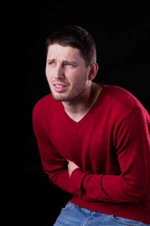 diarrhoea: Young man with stomach ache on black background Stock Photo