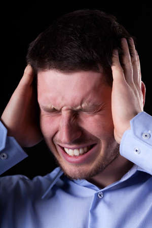 throe: Vertical view of close-up of man with headache Stock Photo
