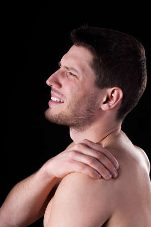 Naked man suffering from shoulder pain, vertical photo