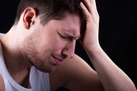 throe: Man with strong migraine isolated on black