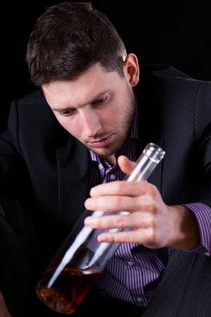 tomando alcohol: Hombre elegante beber alcohol despu�s del trabajo, vertical Foto de archivo