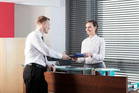 recepcionista: Vista horizontal de una recepcionista mujer y hombre de negocios Foto de archivo