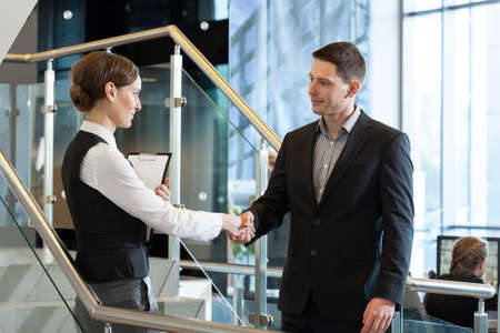 Businesswoman and businessman shaking hands before meeting photo