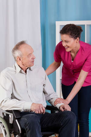 Disabled man on wheelchair and his nurse photo