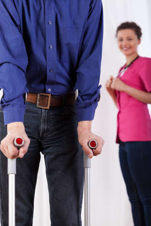 Nurse watching disabled man on crutches, vertical photo