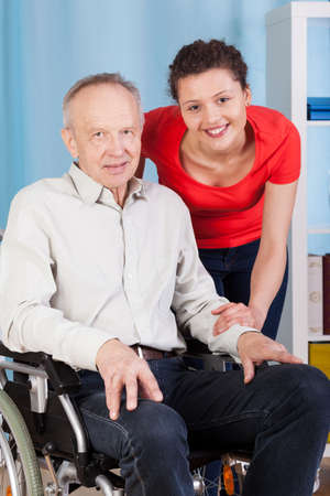 Smiling disabled man and his nurse, vertical photo