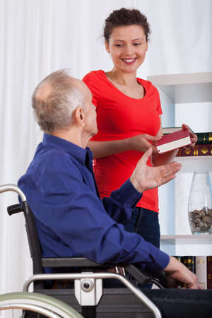 gives: A young woman gives the book a disabled men Stock Photo