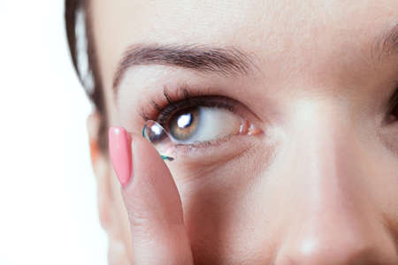 Close-up of inserting a contact lens in female eye Stock Photo
