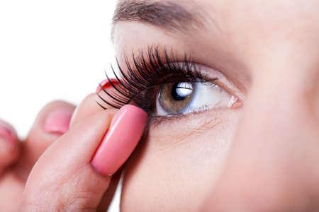 Close-up van een vrouw het toepassen van valse wimpers Stockfoto