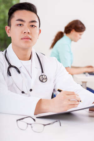 prescribe: Portrait of young asian doctor taking notes