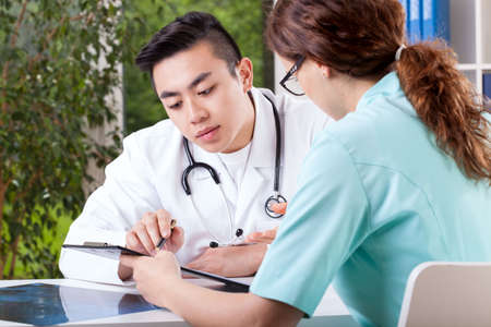 medical examination: Young doctor and nurse interpreting patients results Stock Photo