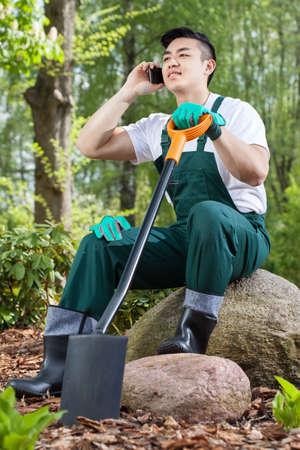gardening gloves: Young asian gardener resting, talking on the phone