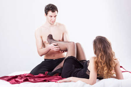 Man taking off tights from womans legs photo