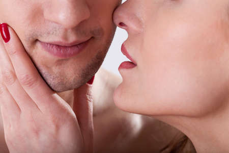 intimate sex: Close-up of woman kissing man to the cheek