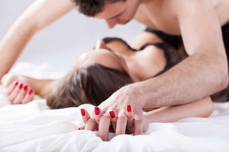 Couple lying on bed having erotic moment