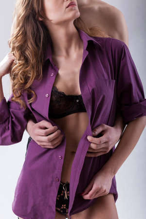 Man undressing woman from purple shirt photo