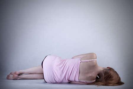 miserable: Skinny girl lying on the floor, horizontal