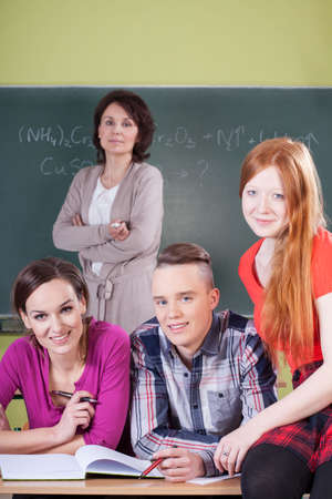 Teacher and students during chemistry lesson, vertical photo