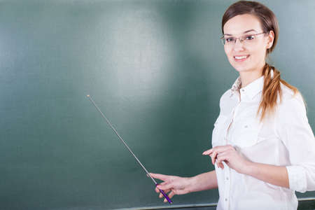 Teacher working next to blackboard at school photo