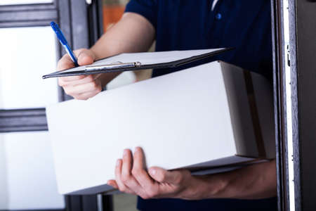 courier delivery: Delivery man supplying pack and asking for a signature