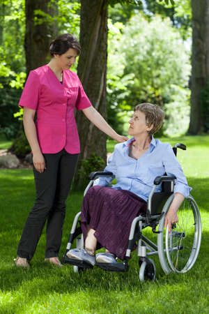 Elderly woman in a wheelchair with a nurse in the park photo