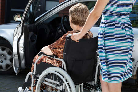 A young woman is carrying an old lady in a wheelchair to the car