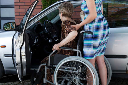disabled person: Young woman helping a disabled lady get in the car