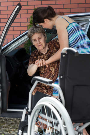 Young woman helping her grandmother get into the car Stockfoto