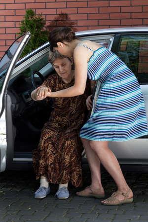 ancianos caminando: Mujer joven que ayuda a las personas con discapacidad para salir del coche