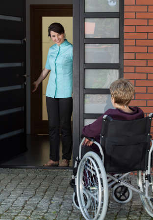 enters: Elderly disabled woman in a wheelchair enters the house