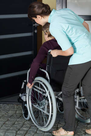 mobility nursing: Young nurse helping a disabled woman to enter the house