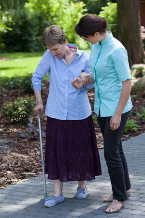 mature adult women: Young nurse goes for a walk with the old lady on crutches Stock Photo