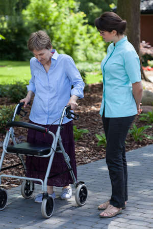 Nurse watches as an elderly woman walks with walker photo