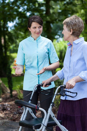The nurse encourages older woman for walking in garden photo