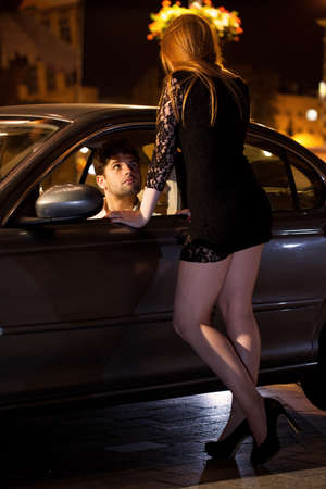 Young man in car chatting up prostitute photo