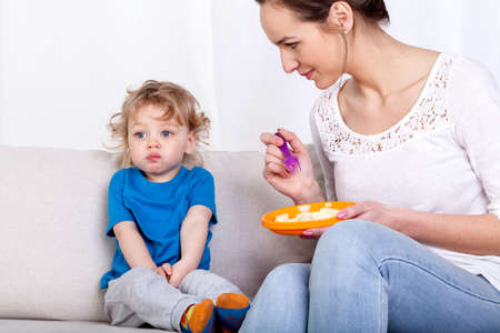 fussy: Young woman feeding her fussy child while sitting on a sofa