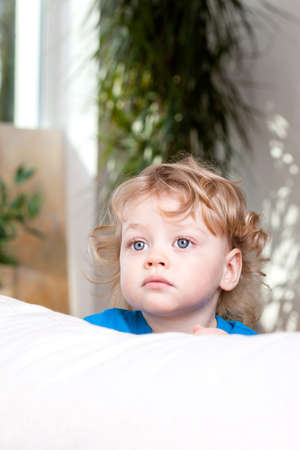 Young child looking in the distance over a bed photo