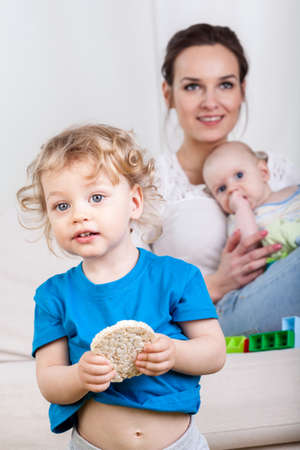 baby rice: Young kid holding a rice wafer with mother and baby in background