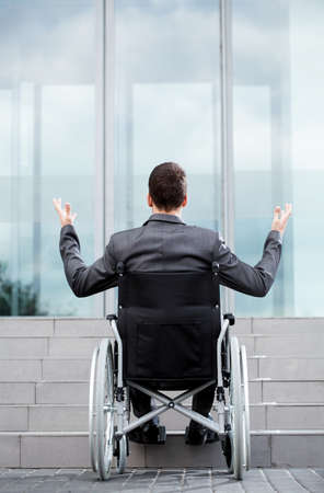 Back view of a disabled man in front of stairs, vertical