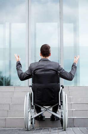 persona en silla de ruedas: Vista posterior de un hombre discapacitado en frente de las escaleras, vertical