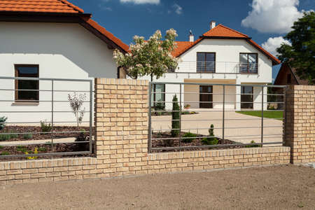 outbuilding: View of beautiful house with modern fence Stock Photo