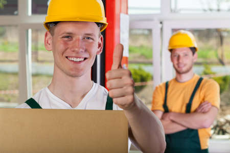Smiling warehouseman in hardhat showing thumbs up sign photo