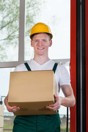 storekeeper: Portrait of a workman holding a cardboard box at warehouse