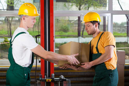 warehouseman: Side view of a two logistics workers at storehouse