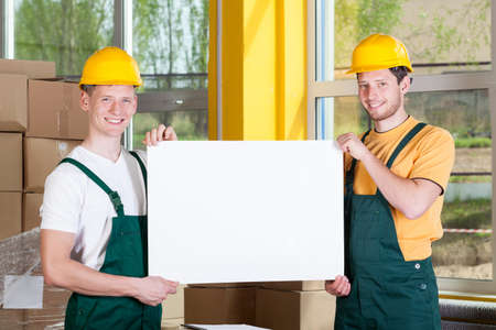 Smiling warehouse workers holding a blank white board photo