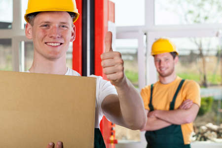 Blue-collar worker showing thumbs up sign, horizontal photo