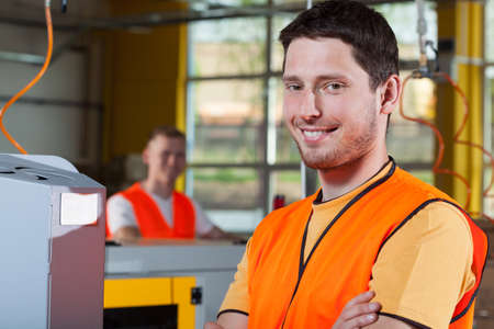 Smiling industrial worker standing with arms crossed at factory