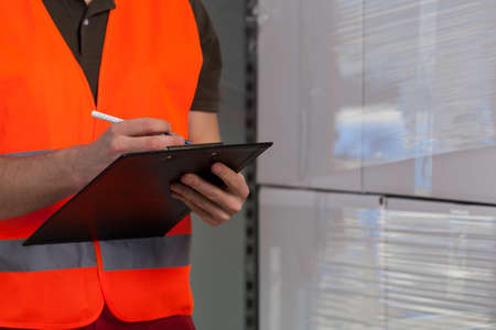 warehouseman: Close-up of a storekeeper signing document on clipboard Stock Photo