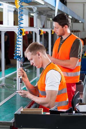 empleados trabajando: Los empleados que trabajan al lado de la máquina en una fábrica
