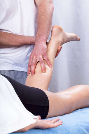 tense: Physiotherapist making the massage of tense calf
